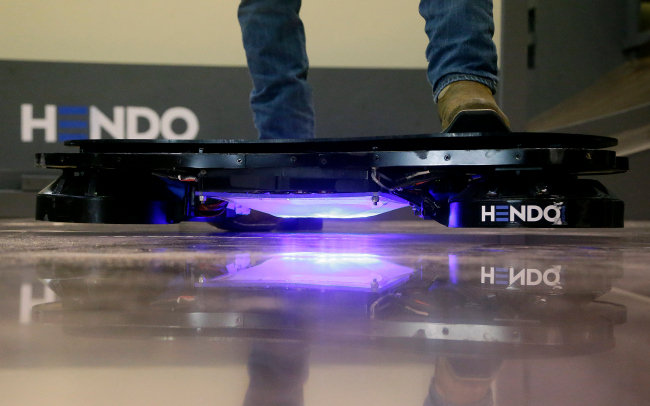 In this Oct. 30, 2014 photo, Arx Pax engineer Garrett Foshay stands over a Hendo Hoverboard in Los Gatos, Calif. Skateboarding is going airborne this fall with the launch of the first real commercially marketed hoverboard which uses magnetics to float about an inch off the ground. (AP Photo/Jeff Chiu)